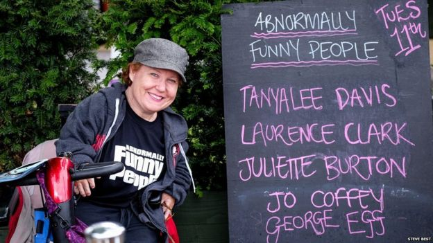 Tanya Lee Davis by a sign advertising the Abnormally Funny People show