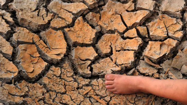 Pie de un niño muy pequeño sobre tierra quebrada por la seca