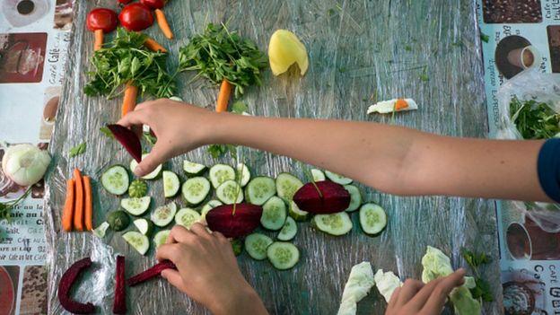 Manos de un niño acomodando verduras sobre una mesa.