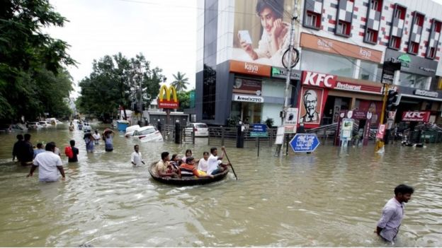 Indian residents make their way through floodwaters in Chennai on December 3, 2015