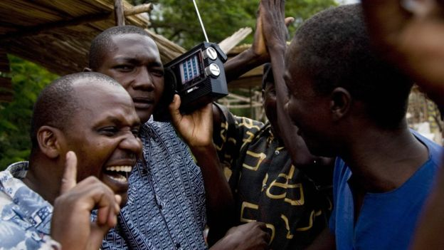 kenyan men listen to radio