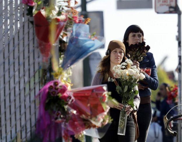 Dos personas llevan flores al lugar tras el incendio.