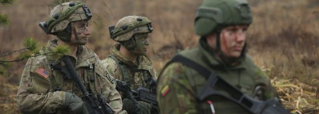 Members of the U.S. 173rd Airborne Brigade (L) and a Lithuanian infantry soldier participate in the Iron Sword multinational military exercises on November 24, 2016 near Pabrade, Lithuania