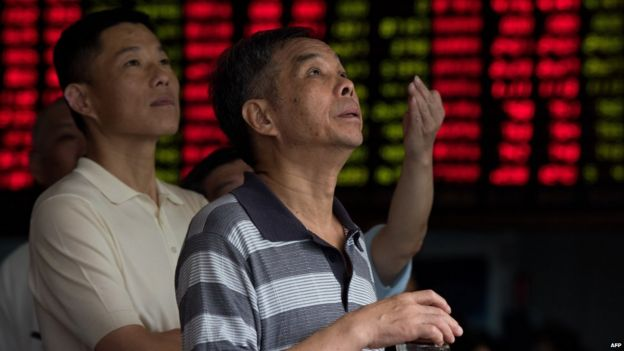 Investors monitor screens showing stock market movements at a brokerage house in Shanghai on 13 August 2015.