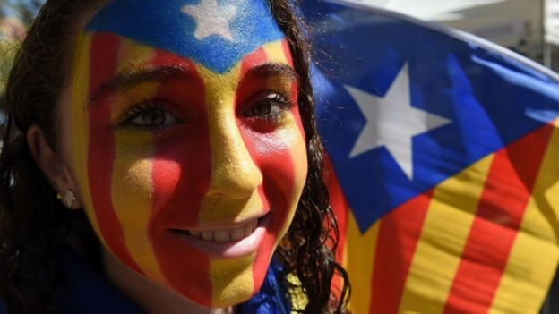 A Catalan demonstrator with her face painted in the pro-independence colours in Barcelona, 11 September