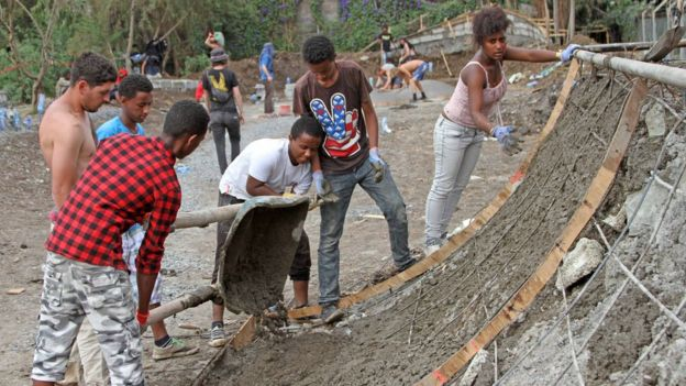 Ethiopian boy pours concrete to make a ramp while four others look on