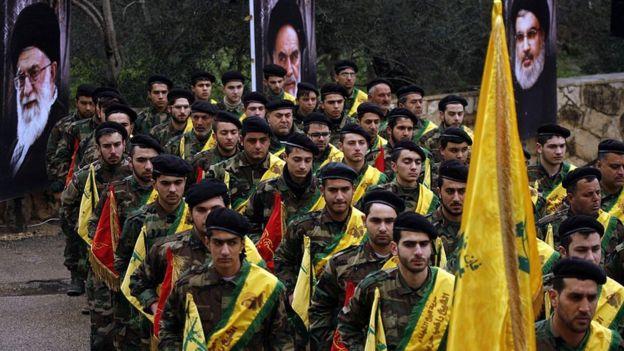 Combatentes do Hezbollah marcham diante de fotos dos aiatolás iranianos
