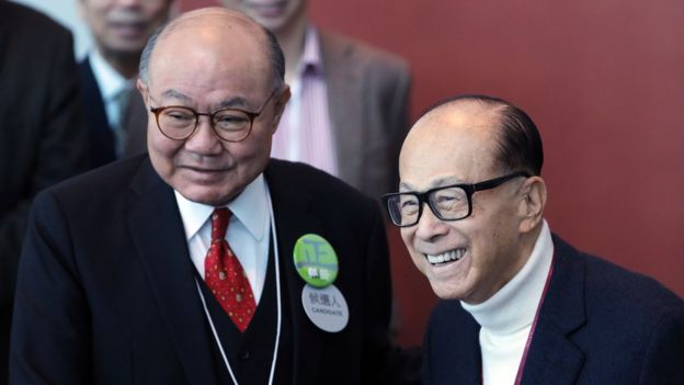 Billionaire Li Ka-shing, chairman of CK Hutchison Holdings Ltd. and Cheung Kong Property Holdings Ltd., right, greets Woo Kwok-hing, a candidate for Hong Kong's chief executive and retired judge, as he arrives at a polling station for the chief executive election in Hong Kong, China, on Sunday, March 26, 2017.