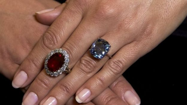A model with a pigeon's blood ruby ring (L) and the cushion-shaped blue diamond ring at Sotheby's in Geneva (11 November 2015)