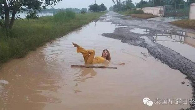 Woman posing in a pothole in Thailand