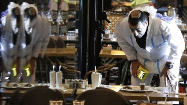 Israeli forensic police officer inspects a restaurant after a shooting at Sarona Market, Tel Aviv, on 8 June 2016