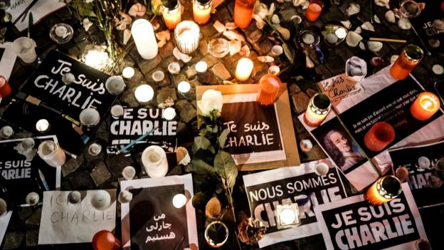 Papers with 'I am Charlie' in various languages displayed are left near candles at a vigil in front of the French Embassy following the terrorist attack in Paris on 7 January 2015 in Berlin, Germany