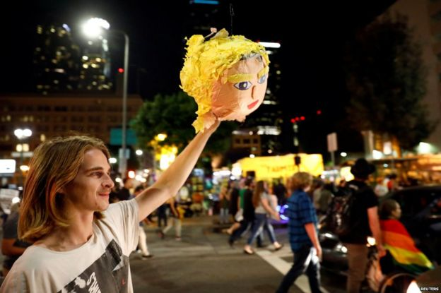 A demonstrator holds a pinata head of Donald Trump in Los Angeles in protest , 10 November