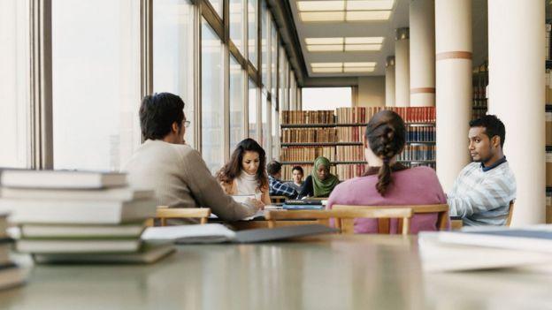 Universitários em biblioteca