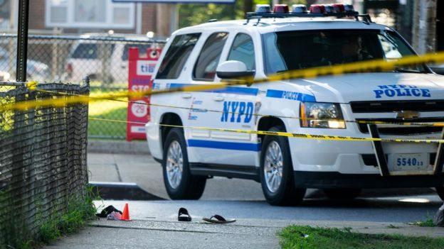 Sandals lay on a street corner at the crime scene, Saturday, Aug. 13, 2016, not far from the Al-Furqan Jame Masjid Mosque in the Ozone Park neighborhood of Queens, New York