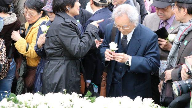中枢纪念仪式结束后,许多民众排队献花,还有人低头啜泣。