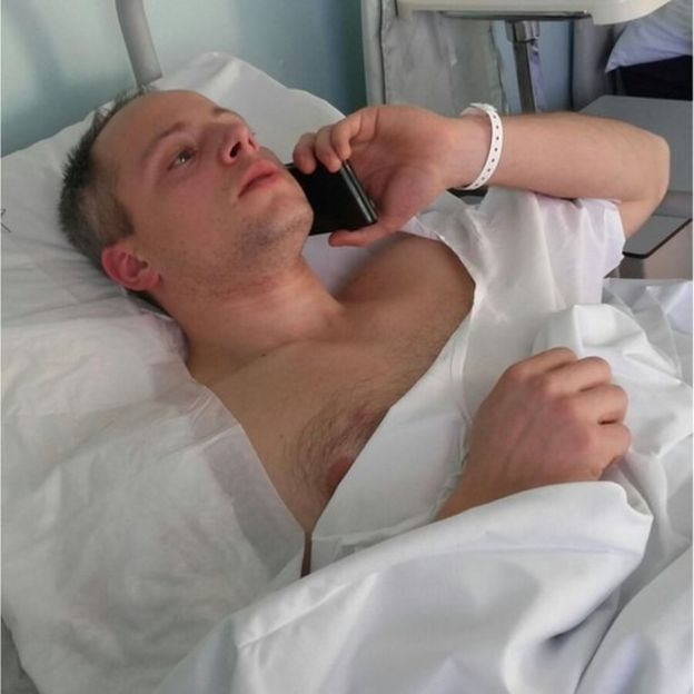 Injured police officer Cristian Movio talks on the phone in hospital, bandages on his shoulder