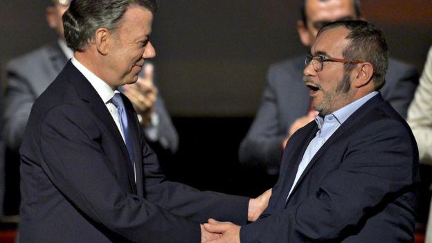 Juan Manuel Santos y Timochenko estrechándose de manos.
