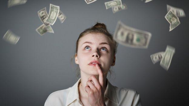 Una joven que ve caer billetes desde arriba