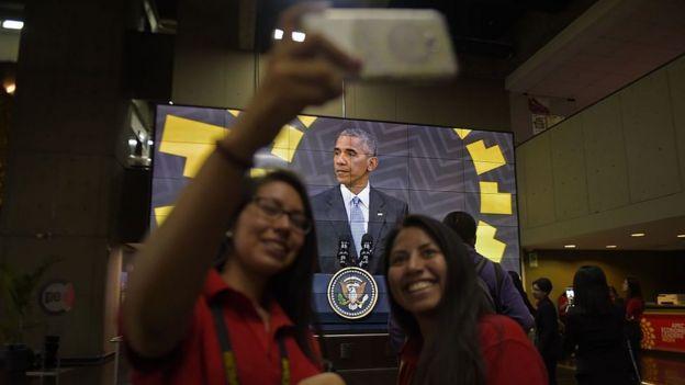 Chicas tomándose una selfie con Obama en el fondo, en Lima