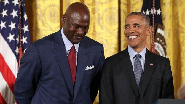Barack Obama smiles up at National Basketball Association Hall of Fame member and legendary athlete Michael Jordan