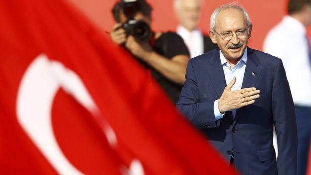 CHP lideri Kemal Kılıçdaroğlu Türk bayrakları arasında kürsüde yürürken görülüyor.
