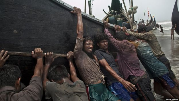 Rohingya men push a fishing boat to shore on 4 July, 2015 in Shamlapur, Bangladesh