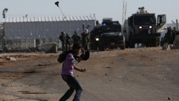 Palestinian swings sling towards Israeli troops near Ramallah (file photo)