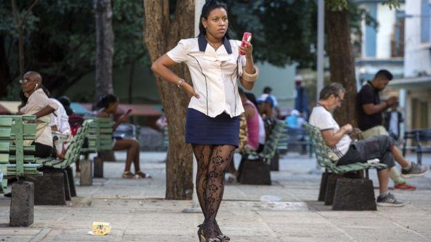 Una mujer en una calle con el celular en la mano.