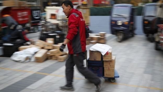 A delivery worker pulls a cart loaded with goods past workers sorting parcels for their customers in Beijing