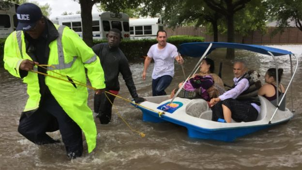 A lone police officer pulls a family to safety from flooding in the western suburbs of Houston on Monday August 28 (pic: James Cook, BBC)