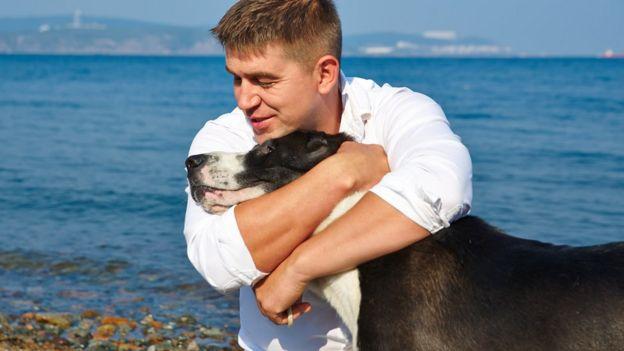 Homem abraçado a cão