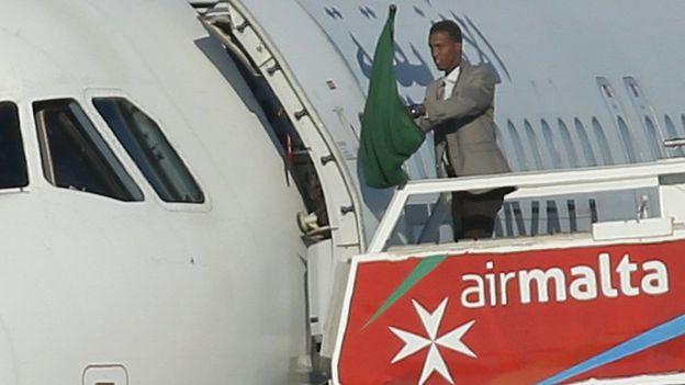 Un hombre no identificado salió del avión enarbolando una bandera libia de la era de Gaddafi.