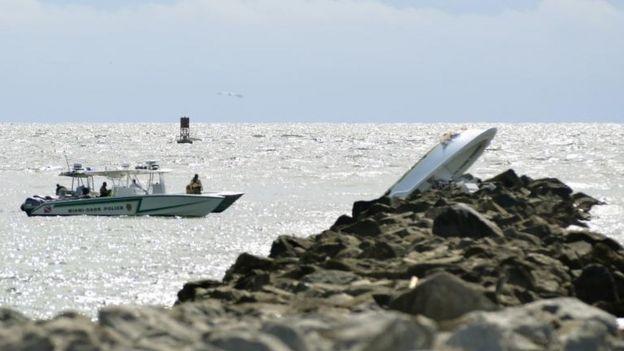 Embarcación volcada sobre una escollera.
