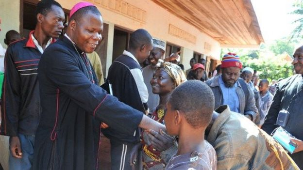 Bangui's archibishop Dieudonne Nzapalainga (L) shakes hands with people after a meeting gathering christian and muslim community members on October 8, 2013 in Bangassou