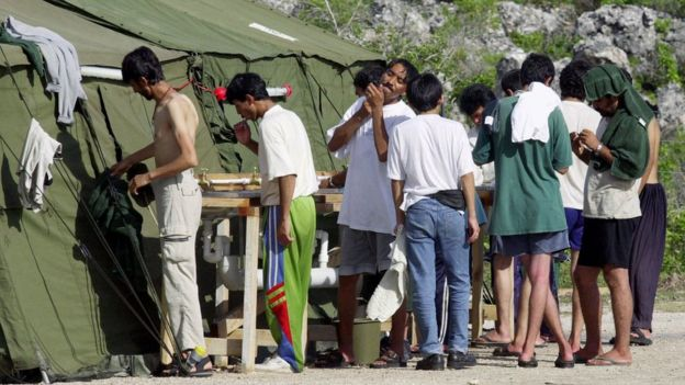 Men wash at a refugee camp on the Island of Nauru, 21 September 2001