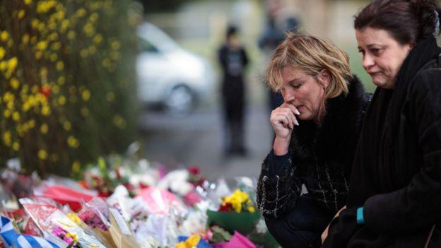 Mujeres mostrando su tristeza dejan tributos en la puerta de la casa de George Michael en Oxfordshire