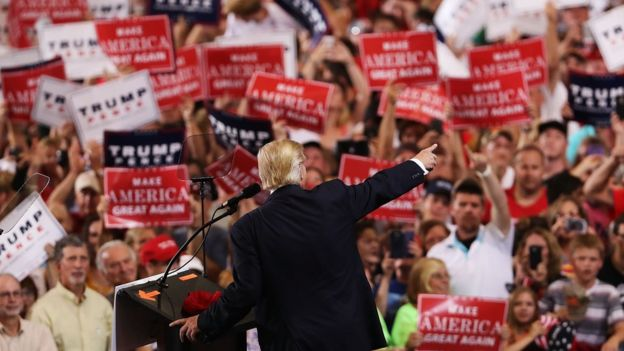 Donald Trump walks past supporters waving signs reading Florida in Melbourne, Florida - 27 September 2016