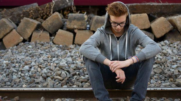 Adolescente mirando al piso