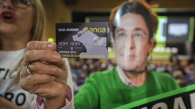 Una mujer exhibe una copia falsa de una tarjeta de crédito
