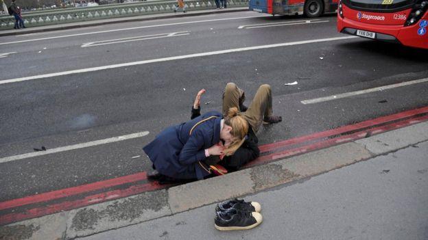 Женщина оказывает помощь пострадавшему на Вестминстерском мосту