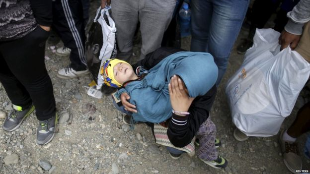 A migrant holds a child as they wait to board a train after crossing the Macedonian-Greek border near Gevgelija, Macedonia, on 8 September 2015