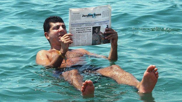 Hombre leyendo el periódico en el mar muerto.