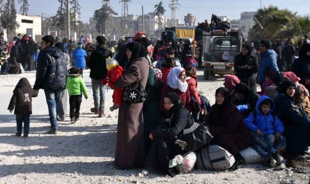Syrians wait at a checkpoint manned by pro-government forces after leaving eastern Aleppo