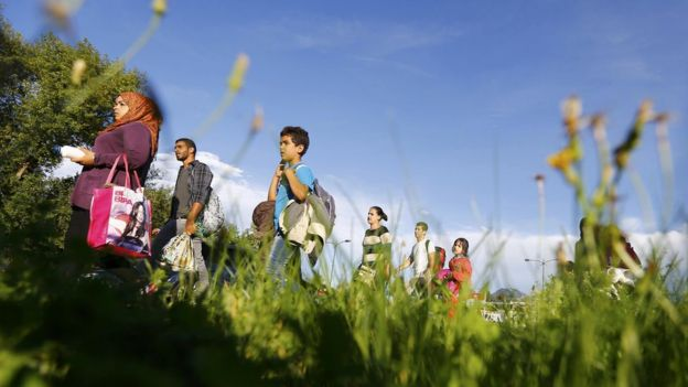 Migrants walk to be registered after crossing the border from Austria in Freilassing, Germany