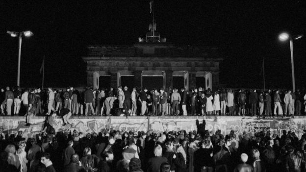 East and West German citizens celebrate as they climb the Berlin Wall at the Brandenburg Gate after the opening of the East German border was announced in Berlin, on 9 November, 1989