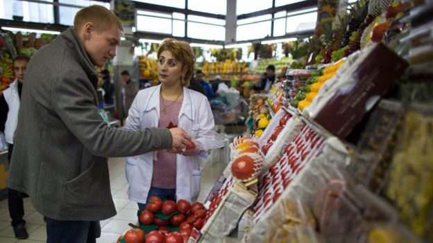 A trader helps a customer to buy tomatoes at Dorogomilovsky food market in Moscow, Russia, Friday, Nov. 27, 2015.