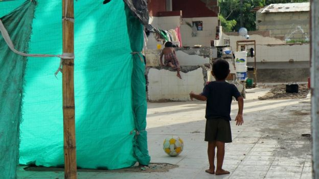 Un niño juega con una pelota de fútbol entre las casitas hechas de palos y plásticos.