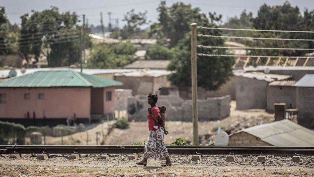 A woman walks with her baby on her back on the oustkirts of Lusaka, Zambia