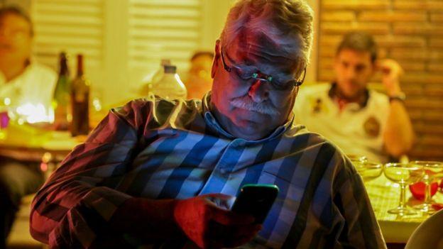 Hombre de mediana edad usando el celular